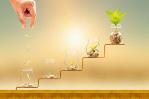 Hand dropping coins into jars with coins, increasing in height and with plants emerging