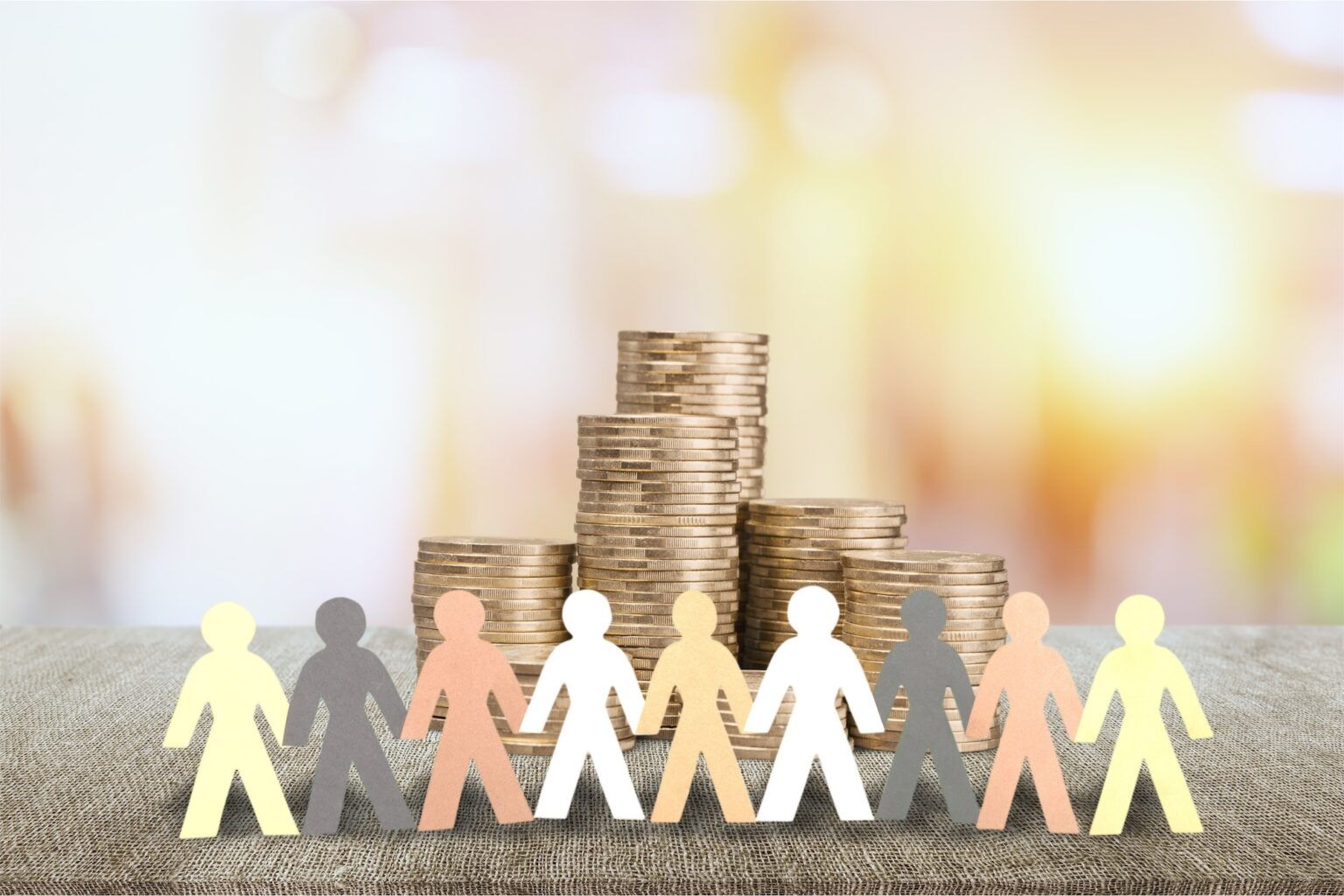 Paper figurines of diverse people standing in front of stack of coins