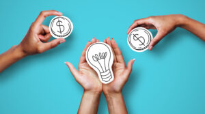 Hands with dollar sign coins and light bulb, against a blue background, representing financing