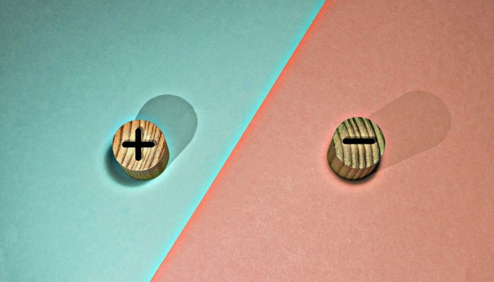 Wooden chips with a plus sign and a minus sign, on a blue and pink background. Representing pros and cons.